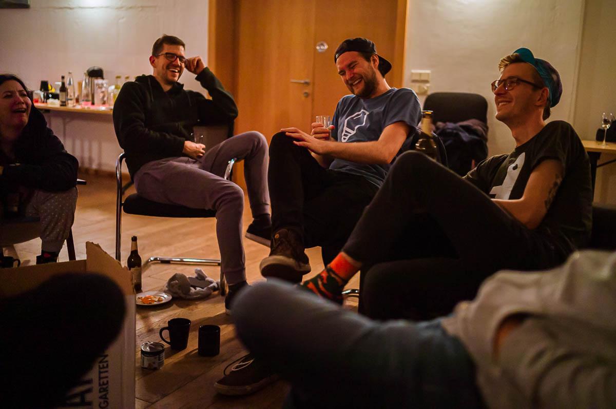 Gruppe lachend im Kreis sitzend
