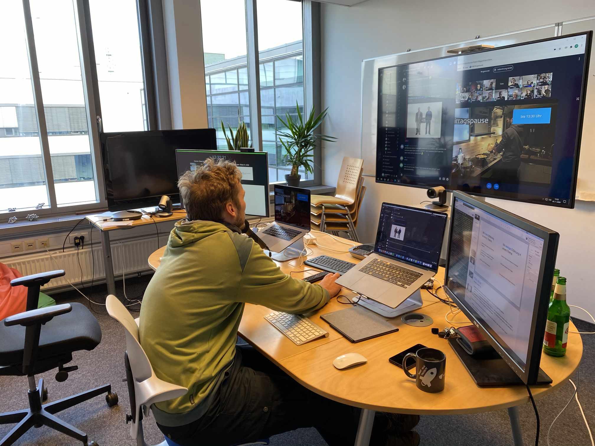 Person an Schreibtisch mit vielen Bildschirmen