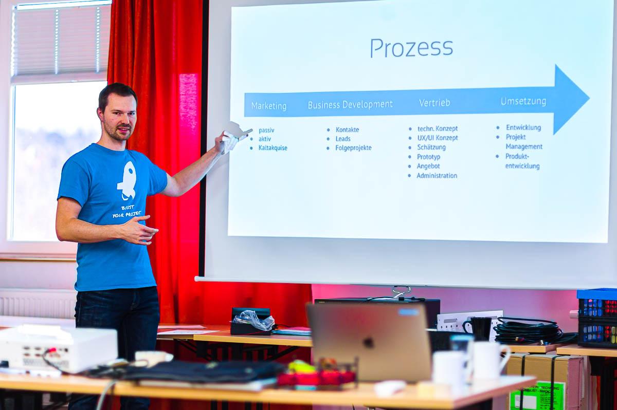 Mann präsentiert und zeigt auf Vortragsfolie